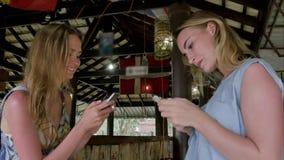 Muchachas bonitas que usan smartphones en barra asiática Foto de archivo