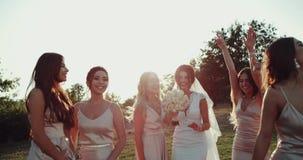 Muchachas bonitas y novia que saltan en hierba y la sonrisa 4K almacen de video