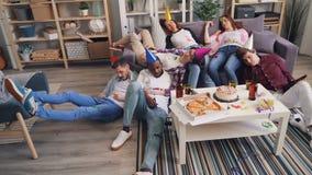 Muchachas borrachas e individuos que duermen en piso y el sofá después de partido alegre en el apartamento almacen de metraje de vídeo