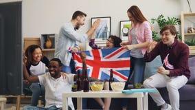 Muchachas británicas e individuos que miran deportes en las banderas que agitan de la TV que celebran la victoria metrajes