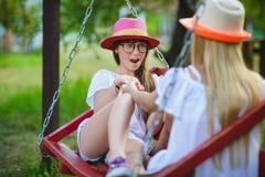 Muchachas caucásicas adolescentes felices sonrientes en el oscilación Fotos de archivo libres de regalías