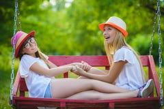Muchachas caucásicas adolescentes felices sonrientes en el oscilación Fotografía de archivo