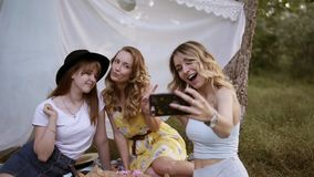Muchachas caucásicas alegres que toman el selfie en smartphone Mujeres lindas jovenes con expresiones faciales sesual el sentarse almacen de video