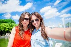 Muchachas caucásicas que hacen fondo del selfie la fuente grande Amigos turísticos jovenes que viajan el los días de fiesta al ai Fotos de archivo libres de regalías