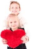 2 muchachas con el corazón rojo en un fondo blanco Imagen de archivo libre de regalías