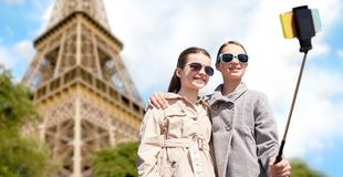 Muchachas con el palillo del selfie del smartphone en la torre Eiffel Imagenes de archivo