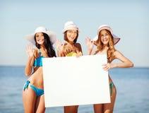 Muchachas con el tablero en blanco en la playa Fotos de archivo