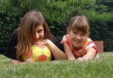 Muchachas con la bola que miente en la hierba Imagen de archivo libre de regalías