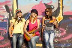 Muchachas con la guitarra y la pared de la pintada Fotografía de archivo libre de regalías