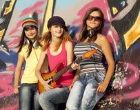 Muchachas con la guitarra y la pared de la pintada Fotos de archivo libres de regalías