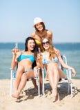 Muchachas con las bebidas en las sillas de playa Imagenes de archivo
