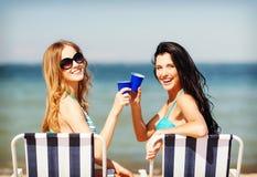 Muchachas con las bebidas en las sillas de playa Imágenes de archivo libres de regalías