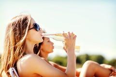 Muchachas con las bebidas en las sillas de playa Fotos de archivo libres de regalías