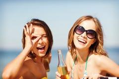 Muchachas con las bebidas en las sillas de playa Imagen de archivo