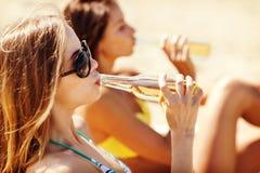 Muchachas con las bebidas en las sillas de playa Imagen de archivo libre de regalías
