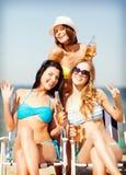Muchachas con las bebidas en las sillas de playa Fotos de archivo