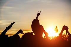 Muchachas con las manos encima del baile, cantando y escuchando la música durante la demostración del concierto en festival de mú Fotos de archivo libres de regalías