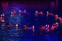 Muchachas con las velas que nadan en un círculo en piscina Imágenes de archivo libres de regalías