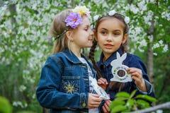Muchachas con los conejitos del juguete que dicen secretos en el oído Fotografía de archivo libre de regalías