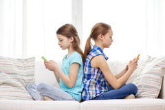 Muchachas con los smartphones que se sientan en el sofá en casa Foto de archivo libre de regalías