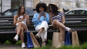 Muchachas con los teléfonos que se sientan en banco después de hacer compras almacen de video