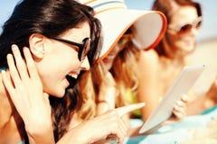 Muchachas con PC de la tableta en la playa Imagenes de archivo