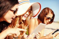 Muchachas con PC de la tableta en la playa Imagen de archivo libre de regalías