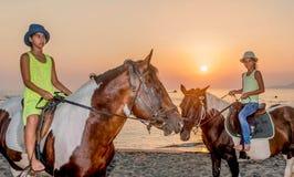 Muchachas con un sombrero en caballos de montar a caballo Fotos de archivo