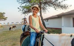 Muchachas con un sombrero en caballos de montar a caballo Fotografía de archivo libre de regalías