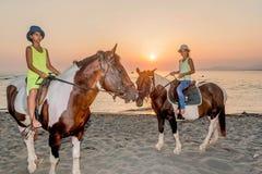 Muchachas con un sombrero en caballos de montar a caballo Fotos de archivo libres de regalías