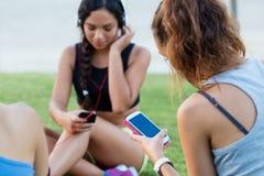 Muchachas corrientes que se divierten en el parque con el teléfono móvil Imagen de archivo libre de regalías