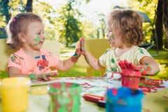Muchachas de dos años que pintan con las pinturas del cartel junto contra césped verde Fotos de archivo