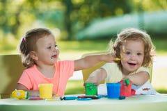 Muchachas de dos años que pintan con las pinturas del cartel junto contra césped verde Fotos de archivo libres de regalías