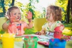 Muchachas de dos años que pintan con las pinturas del cartel junto contra césped verde Imagen de archivo libre de regalías