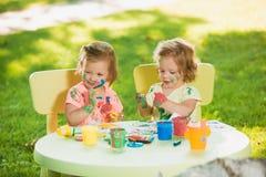 Muchachas de dos años que pintan con las pinturas del cartel junto contra césped verde Imagen de archivo