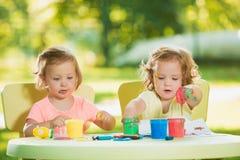 Muchachas de dos años que pintan con las pinturas del cartel junto contra césped verde Imagenes de archivo