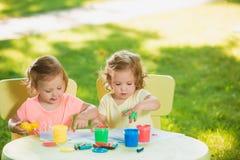 Muchachas de dos años que pintan con las pinturas del cartel junto contra césped verde Fotografía de archivo