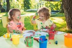 Muchachas de dos años que pintan con las pinturas del cartel junto contra césped verde Foto de archivo