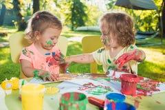 Muchachas de dos años que pintan con las pinturas del cartel junto contra césped verde Foto de archivo libre de regalías