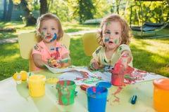 Muchachas de dos años que pintan con las pinturas del cartel junto contra césped verde Fotografía de archivo libre de regalías