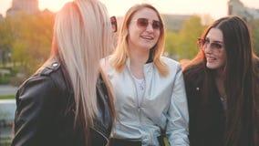 Muchachas de la amistad de las mujeres que cuelgan hacia fuera el parque de la ciudad metrajes