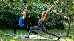 Muchachas de la aptitud que hacen la yoga al aire libre Virabhadrasana almacen de video