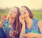 Muchachas de la belleza que soplan burbujas de jabón en parque de la primavera Foto de archivo libre de regalías