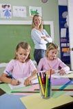 Muchachas de la escuela que escriben en cuadernos con el profesor Imagen de archivo