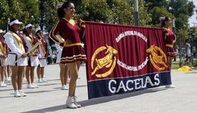 Muchachas de la marcha de la banda que sostienen una bandera Imagen de archivo
