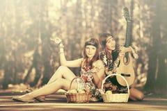 Muchachas de la moda de los jóvenes con las cestas de fruta en bosque del verano Imágenes de archivo libres de regalías