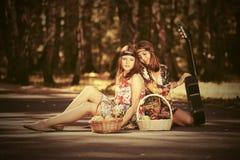 Muchachas de la moda de los jóvenes con las cestas de fruta en bosque del verano Fotografía de archivo
