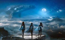 Muchachas de la persona que practica surf que se colocan sobre las nubes que miran sueño de la fantasía foto de archivo libre de regalías