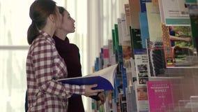 Muchachas de la universidad que se encuentran delante del estante para libros mientras que el elegir reserva para leer almacen de video