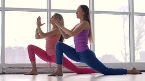 Muchachas de la yoga que hacen la yoga junta contra fondo grande de las ventanas almacen de metraje de vídeo